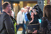 Saturday  17 December 2016<br /> Pictured: A woman cheers as she takes a helmet from a police officer <br /> Re: Swansea City Centre and the notorious Wind street, often nicknamed 'Wine Street' is packed full of Christmas jumpers and glitzy dresses as thousands head to office dos across the UK in the biggest party night of the year.