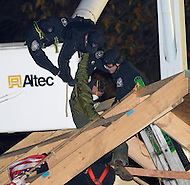 "December 4, 2011  (Washington, DC)  U.S. Park Police officers struggle to remove a man from the top of a structure built by OccupyDC protesters at the McPherson Square park.  The man, whose name is ""Mark"" according to a fellow occupier, was the last of 31 people arrested by police.  The structure was being built to help Occupy protesters make it through the winter months.  At this point, a Park Police spokesman said there were no plans to dismantle the entire encampment and completely remove protesters.  (Photo by Don Baxter/Media Images International)"