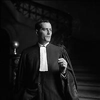 """Palais de Justice. 8 juin 1961. Plan taille de Maître Gaillardo (avocat de l'accusé Paul Carrère), en tenue, vue de face, cigarette à la main. Cliché pris dans le cadre de l'affaire de la """"Tournerie des drogueurs"""" dont le procès s'est ouvert à Toulouse le 5 juin 1961. Observation: Affaire de la """"Tournerie des drogueurs"""" : Procès qui s'est ouvert aux assises de Toulouse le 5 juin 1961, sous la présidence de M. Gervais (conseiller doyen). Sur le banc des accusés se trouvent François Lopez, Raoul Berdier, Marie-Thérèse Davergne (Maïté) et d'autres malfaiteurs toulousains (Camille Ajestron, Henri Oustric, Raymond Peralo, Marcel Filiol, Paul Carrère, Charles Davant et François Borja). Outre les accusations pour association de malfaiteurs, ils comparaissent pour l'assassinat de Jean Lannelongue, propriétaire du Cabaret la Tournerie des Drogueurs (rue des Tourneurs) dans la nuit du 3 au 4 janvier 1959, au cours d'une tentative de racket."""
