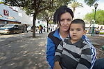"Anaivis Machado, a psychologist, and her 3-year old son Dario sit in the Plaza Benito Juarez in Nuevo Laredo, Mexico, on March 3, 2017. They left their home in Santa Clara, Cuba, bound for the United States, but are now waiting close to the U.S.-Mexico border, caught in limbo by the elimination in January of the infamous ""wet foot, dry foot"" policy of the United States. They are not allowed to enter the U.S. yet don't want to return to Cuba. Many of the city's churches have become temporary shelters for the immigrants, and congregations rotate responsibility for feeding the Cubans. Such solidarity from ordinary Mexicans is being tested these days, as not only are the Cubans stuck at the border, but the U.S. has stepped up deportations of Mexican nationals, while at the same time detaining many undocumented workers from other nations and simply dumping them on the US-Mexico border. Machado's husband is a member of the Methodist Church in Cuba."