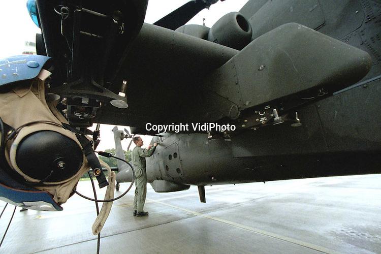 """Foto: VidiPhoto..GILZE-RIJEN - Drie AH-64A Apache-helicopters van de Koninklijke Luchtmacht zijn vrijdag van vliegbasis Gilze-Rijen teruggevlogen naar Duitsland. De Koninklijke Luchtmacht is begonnen met het terugbrengen van de twaalf geleende Apache-helicopters, type Alpha. Deze zogenoemde """"lease-bakken"""" worden naar vliegbasis Rhein-Main in Frankfurt gevlogen, waar ze worden opgepikt voor transport naar en hergebruik in de VS. De helicopters deden sinds 1996 dienst bij het 301 Squadron van de Nederlandse Luchtmacht. Het wachten is op de splinternieuwe Delta-versie, waarvan er dertig zijn besteld. Foto: Voor vertrek wordt het gevechtstoestel uitgebreid gecontroleerd."""