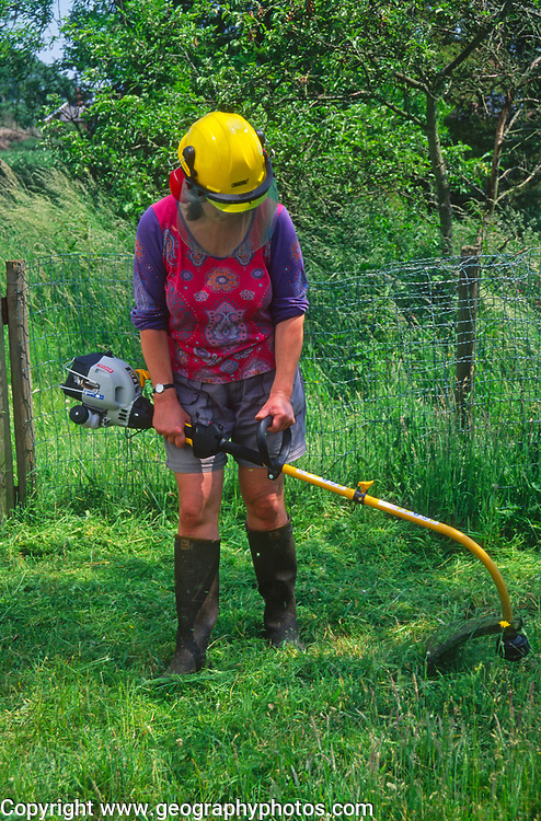 AREHX9 Woman using a strimmer to cut long grass lawn in her cottage garden during summer, Suffolk, England