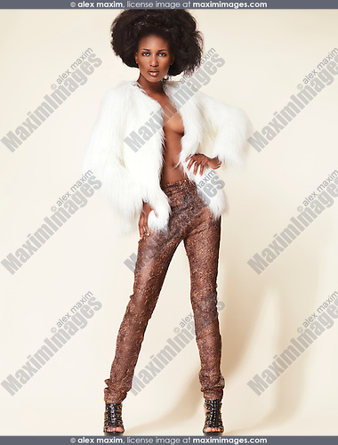 High fashion photo of a young african-american woman wearing a white fur jacket and leggings isolated on beige background