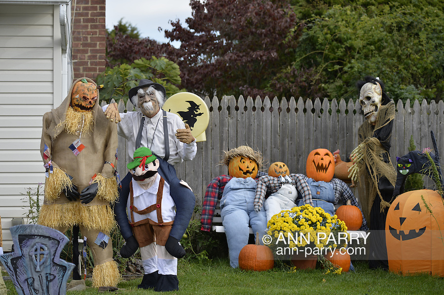 Merrick, New York, USA. October 29, 2016. Second from left,JIM JOHNSON, of Merrick, wearing a Munchkin costume from Wizard of Oz, is standing outside his front yard decorated in a scary spooky Wizard of Oz theme, to entertain people as they walk across the street to the entrance of Fraser Park for the 2016 annual Merrick Spooktacular hosted in part by the North and Central Merrick Civic Association (NCMCA). JOHNSON's hand rested on a ghoulish, gruesome Straw Man lawn decoration, with a daggner plunged into its pumpkin head.