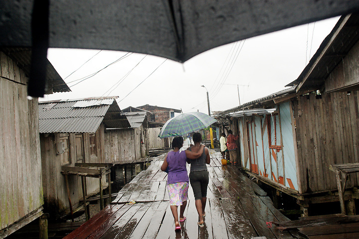 NUQUÍ, EL CHOCO, COLOMBIA -- DECEMBER:  A pair of friends walk arm in arm under an umbrella through the town of Nuqui, December 12, 2005. Nuquí is a small town on Colombia's isolated and untamed Pacific coast, an area sandwiched between endless miles of trackless rainforest and the Pacific Ocean. (Photo by Dennis Drenner/Aurora).