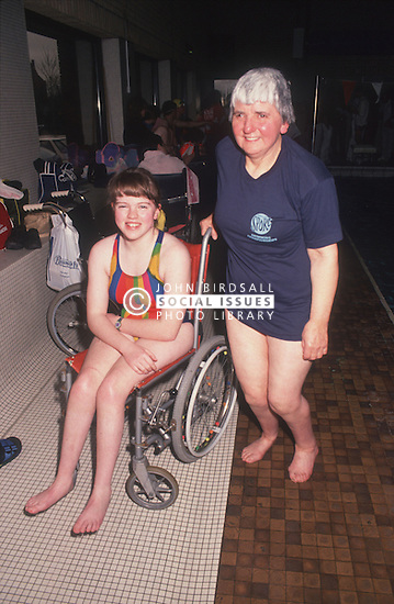 Carer and young girl with disability; who is wheelchair user; wearing swimming costume,
