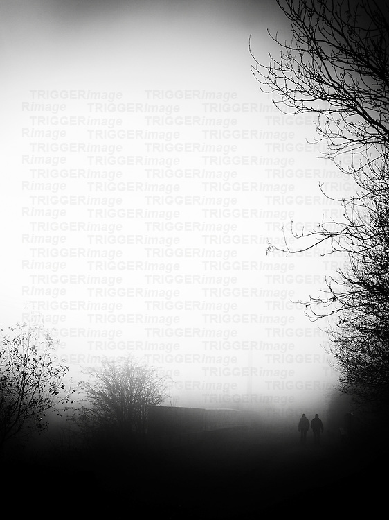 Couple walking along a track, with trees and a dense heavy fog