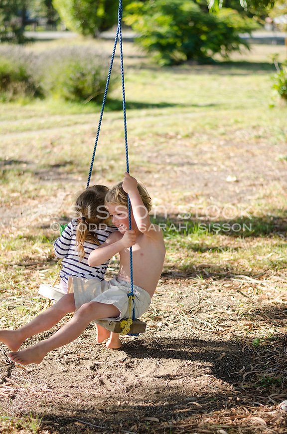 Young boy smiling and sharing a rope swing with young girl on a summers day, New Zealand - stock photo, canvas, fine art print