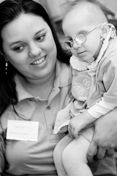 Terra Orr and her daughter Amy at the Share and Care Network's annual retreat held at the Doubletree Guest Suites Hotel in Boston on May 20, 2006. <br /> <br /> The Share and Care Network was created in 1981 by Pat Cahill when her son Scott was diagnosed with Cockayne Syndrome.  A rare form of dwarfism, Cockayne Syndrome is a genetically determined condition whose symptoms include microcephaly, mental retardation, progressive blindness, progressive hearing loss, premature aging, and a shortened lifespan averaging 18 years.  Those afflicted have distinctive facial features, including sunken eyes, pinched faces, and protruding jaws as well as distinctive gregarious, affectionate personalities.<br /> <br /> Because of the rarity of the condition (1/1,000 live births) and its late onset (characteristics usually begin to appear only after one year), many families and physicians are often baffled by children whose health begins to deteriorate after normal development.  It was partly with this in mind that the Share and Care Network was formed, to promote awareness of this disease as well as to provide a support network for those families affected.  In 1998 it began organizing an annual retreat, which has grown from three families in its inaugural year to more than 30 today.  Although the retreat takes place in the United States, families from as far as Japan arrive for this one weekend out of the year to share information and to support one another.