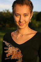 A portrait of a young woman holding flowering grass in a field in Hawai'i.