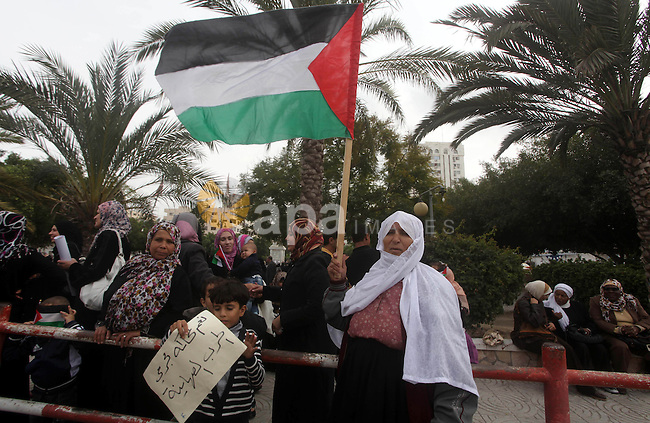 Palestinian women hold national flags during a rally to support reconciliation between rival Palestinian factions in Gaza city on 04 Dec, 2012. Palestinian President Mahmud Abbas pledged Sunday to resume efforts at reconciliation between rival Palestinian factions as he returned from a successful bid for upgraded UN status. Photo by Ashraf Amra