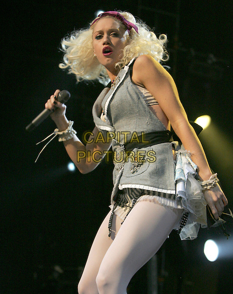 GWEN STEFANI.performs live at The 2004 KROQ Almost Acoustic Christmas Concert, Night One, held at The Universal Ampitheatre in Universal City, California, USA,.December 11th 2004..half length concert live gig music stage white tights alice band waistcoat dress brooch broach belt.Ref: DVS.www.capitalpictures.com.sales@capitalpictures.com.©Capital Pictures.