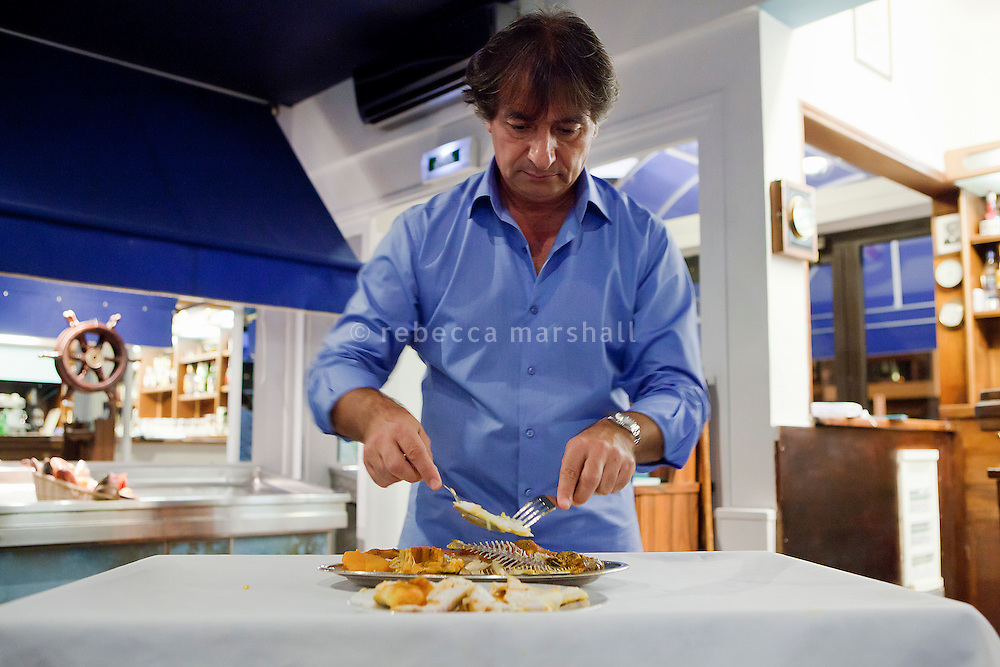 Pascal Visciano, owner of restaurant 'Le Calypso', debones fish to serve bouillabaisse in front of diners in the restaurant, Marseille, France, 25 August 2012. Pascal's grandfather was a fisherman in Marseille and had the idea to open a fish-only restaurant in 1962, which has remained in the family ever since.