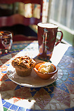 USA, Oregon, Ashland, interior table detail at the colorful Morning Glory Restaurant on Siskiyoui Blvd during breakfast, pumpkin oat muffin served with a cafe late and cranberry juice