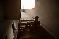 August 2017. YPG Media Centre, Raqqa, Syria.<br /> Foreign volunteer fighter 'Macer Gifford' sits on his own in a stairwell near to the United States military base as he tries to get on the internet to message home.<br /> The MFS (Syriac Military Council) are a group of Assyrian Christians who fight alongside the Syrian Democratic Forces in the fight to topple ISIS.<br /> Photographer: Rick Findler