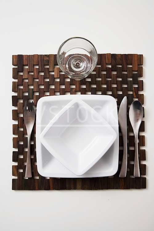 vertical place setting still life restaurant dining special occasion modern contemporary flute glass glassware plate dish dishes bowl dinnerware wooden placemat eating formal elegant fancy silverware table