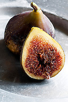 A fresh fig cut into half reveals its red flesh and seeds