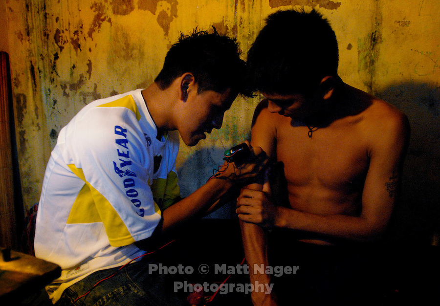 Rene Uribe, right, and his friend sit and give each other tatoos during a rainy Saturday in Eterezama, Bolivia.