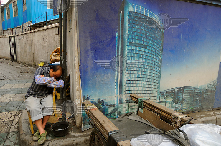 Man sleeping on a chair next to image of future high rise building.