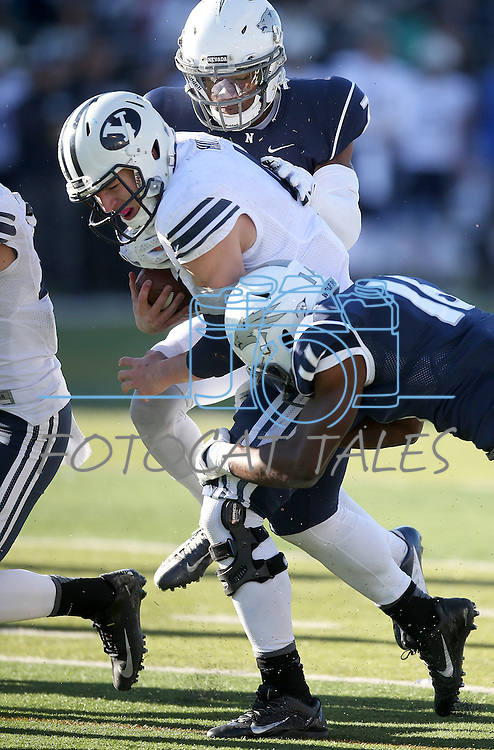 BYU quarterback Taysom HIll (4) is tackled by Nevada defenders Markus Smith (7), center, and Kaodi Dike (16) during the second half of an NCAA college football game in Reno, Nev., on Saturday, Nov. 30, 2013. BYU defeated Nevada 28-23. (AP Photo/Cathleen Allison)