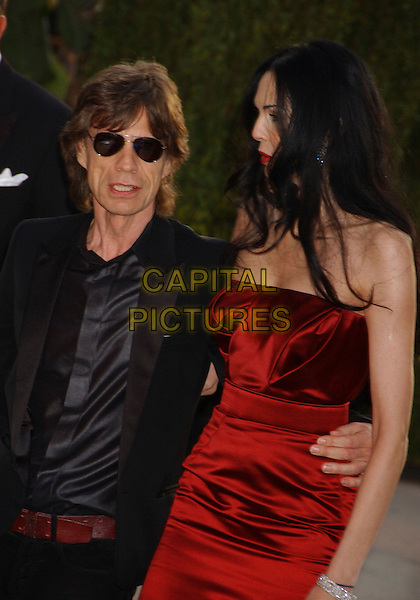 MICK JAGGER & L'WREN.Vanity Fair Oscar Party held at Morton's, West Hollywood, California, USA. .March 5th, 2006.Photo: Gary Boas/AdMedia/Capital Pictures.Ref: GB/ADM.half length sunglasses shades couple red dress black.www.capitalpictures.com.sales@capitalpictures.com.© Capital Pictures.