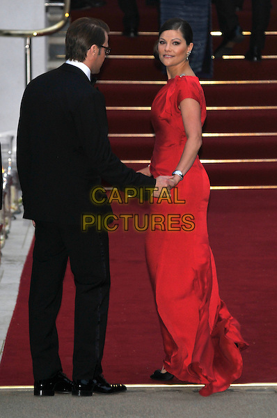 PRINCE DANIEL DUKE OF VASTERGOTLAND, CROWN PRINCESS VICTORIA OF SWEDEN.Gala pre-wedding dinner held at the Mandarin Oriental Hyde Park, London, England. 28th April 2011 in London, England..royal royalty kate catherine middleton prince william full length black tuxedo red dress married husband wife hand holding back behind rear looking over shoulder . CAP/PL.©Phil Loftus/Capital Pictures..