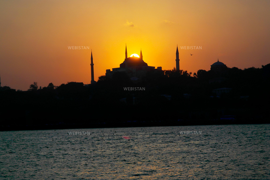 Turkey, Istanbul, Sailing from the Asian side of Istanbul to the Sirkeci District, October 5, 2012The view of Hagia Sophia at sunset, taken from a ferry.Hagia Sophia (meaning Holy Wisdom) is one of the most renowned monuments in Istanbul and the most important Byzantine structure. Construction of the original Hagia Sophia began in the year 360 by the first Christian Emperor, Constantine the Great. The church was reconstructed from 408-450 and then demolished during the Nika riots of 532. The current structure was rebuilt from 532-537 under the supervision of Emperor Justinian I. The basilica served as a Greek Orthodox Cathedral and then became a Roman Catholic Church after the 1204 attack by the Crusaders. When Fatih Sultan Mehmed II conquered Constantinople in 1453, he converted Hagia Sophia into a mosque. Hagia Sophia served as the principal mosque of Istanbul for almost 500 years. In 1934, under Turkish president Mustafa Kemal Ataturk, Hagia Sofia was secularized and turned into the Ayasofya Museum.   <br /> Turquie, Istanbul, District Sirkeci sur la rive asiatique d'Istanbul, 5 octobre 2012Au crepuscule, vue sur la basilique Sainte-Sophie, prise d'un ferry. Hagia Sophia ( signifiant Sainte Sagesse ) est l'un des monuments les plus celebres d'Istanbul et sa structure byzantine en est la plus importante. La construction de la basilique Sainte-Sophie a commence en l'an 360 sous le premier empereur chretien, Constantin le Grand. L'eglise a ete reconstruite de 408 a 450, puis demolie durant les emeutes de Nika 532. La structure actuelle a ete reconstruite en 532-537 sous la supervision de l'empereur Justinien I. La basilique a servi de cathedrale orthodoxe grecque et est ensuite devenue une eglise catholique romaine apres l'attaque des Croises en 1204. Lorsque le Sultan Fatih Mehmed II a conquis Constantinople en 1453, il a converti Sainte-Sophie en mosquee. Elle fut la principale mosquee d'Istanbul pour pres de 500 ans. En 1934, sous la presidence turque d
