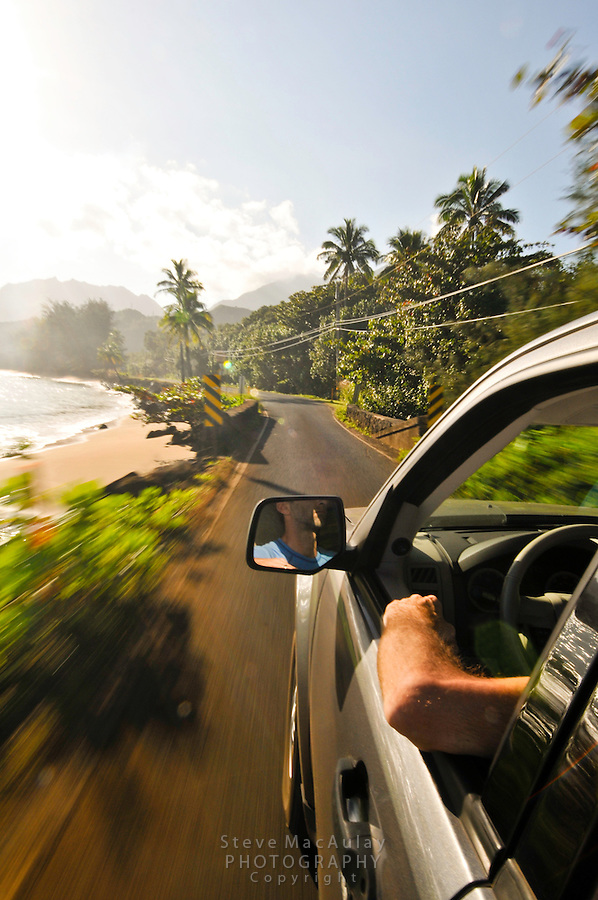 Point of view shot of man driving SUV down road along the north shore of Kauai, just outside of Hanalei.