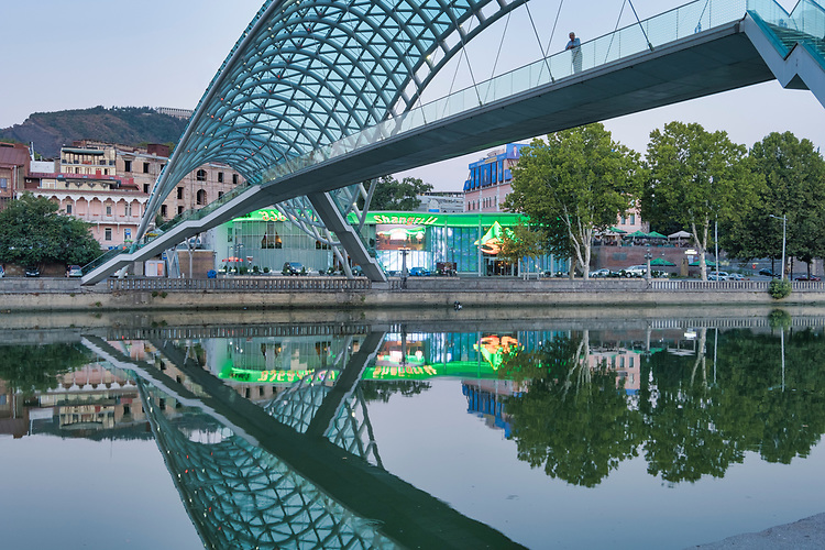 The Bridge of Peace is a bow-shaped pedestrian bridge, a steel and glass construction illuminated with numerous LEDs, over the Kura River in downtown Tbilisi