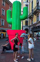 Switzerland. Canton Ticino. Lugano. Town center, A fake giant plastic cactus used as decoration for Longlake Festival stands on Piazza Alighieri Dante. A mother and her children stands by the cactus's red pot. The sun holds in his hands an inflated balloon with the shape of an helicopter. Manor and H&M shops. 23.07.2018 © 2018 Didier Ruef<br />
