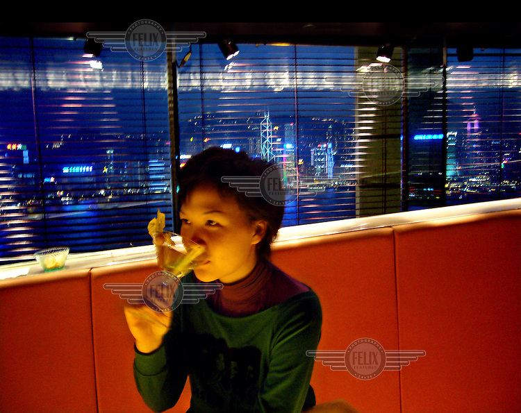 A woman sips at a cocktail in a Hong Kong bar.