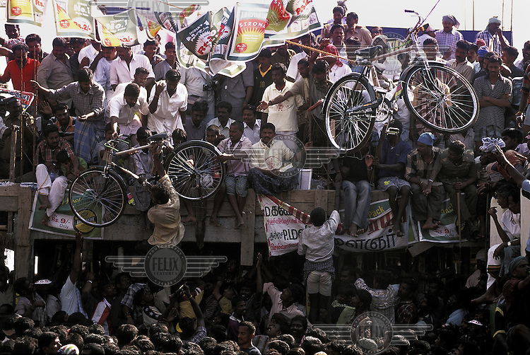 A farmer retrieves his reward of a bicycle, won during the annual Jallikattu bull run, where farmers attempt to mount and 'tame' an enraged bull in order to grab a decoration from its purposely sharpened horns. Anyone who succeeds in doing so can win one of a range of prizes, including the top prize of a bicycle. Each year the bull run results in many injuries and even deaths.  The event is an integral part of Pongal the Tamil New Year/Harvest Festival...