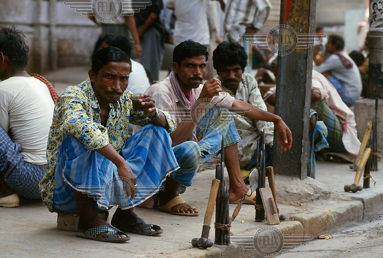 Labourers display their tools while waiting for offers for work in the early morning on Chowringhee..