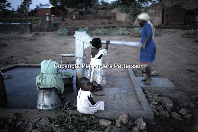 GALUFU, MALAWI NOVEMBER 12: Unidentified young girls fetch water at a water hole, after sunset on November 12, 2005 in Galufu, Malawi. The village has seen an increase in poverty the last few years due to drought and HIV/Aids. There's no electricity in the village. Southern Africa has been hit by a severe hunger crisis due to drought and poverty. An ever-increasing HIV/Aids rate adds to the misery. Malawi is one of the worst hit areas and Galufu village is a typical small village that has become victim of this poverty spiral. <br /> (Photo by Per-Anders Pettersson)