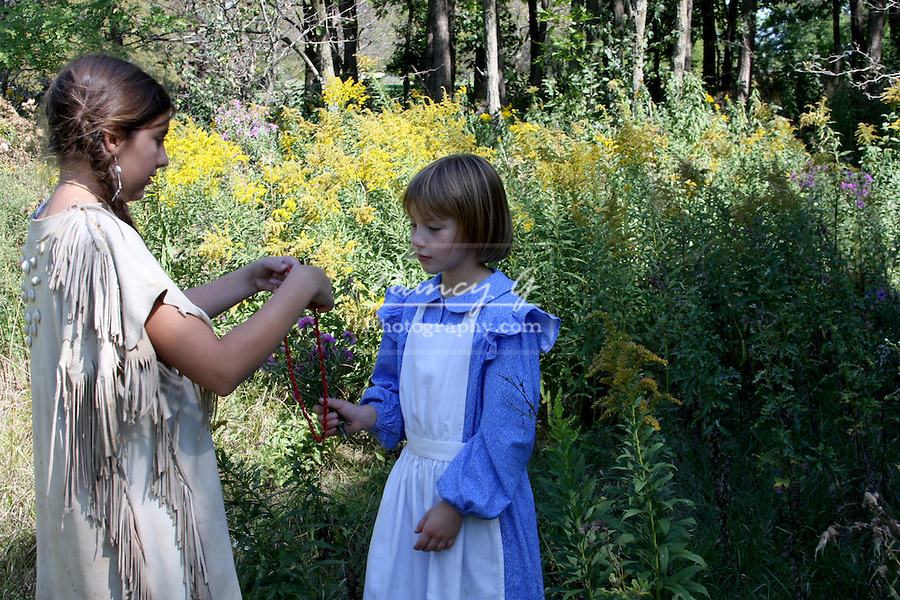 A Native American Indian girl trading beads for flowers with a child in a prairie dress