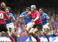 27/03/2004  -  RBS Six Nations Championship 2004 Wales v Italy.Michael Owen passes the ball to Stephen Jones as the Italian  defenders move in.   [Mandatory Credit, Peter Spurier/ Intersport Images].