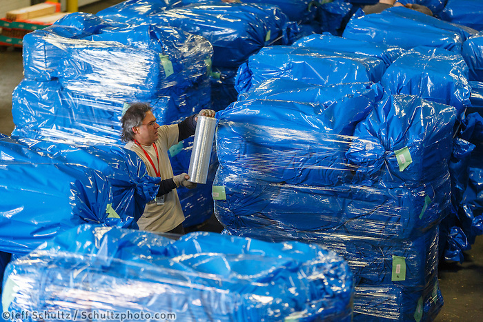 Getting ready for Iditarod 2016, volunteers   as  others bag, zip-tie, stack and shrinkwrap pallets of straw and hay on Thursday, February 11, 2016.  Nearly 1700 bales will be sent out to over 20 checkpoints along the trail. Iditarod 2016