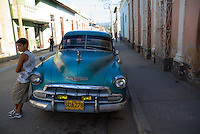 Young boy leaning against a classic American car, Trinidad, Sancti Spiritus, Cuba.