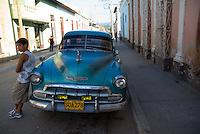 Young boy leaning against a classic American car, Trinidad, Sancti Spiritus, Cuba.