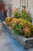 Cuts stone raised planting bed on flag stone patio in small space garden