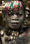 Young girl with face and body painted, shell and beaded head gear, Mursi Tribe, Mago National Park, Lower Omo Valley, Ethiopia, portrait, person, one, tribes, tribal, indigenous, peoples, Southern, ethnic, rural, local, traditional, culture, primitive, Africa
