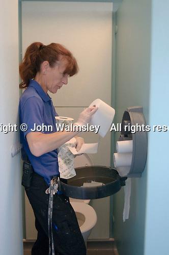 Cleaner replacing toilet rolls,  State Secondary Roman Catholic school.