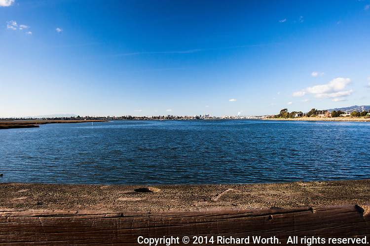 A rough, creased wooden observation deck railing over the San Leandro Bay waters, with Oakland, California's skyline on the horizon and blue sky overhead.