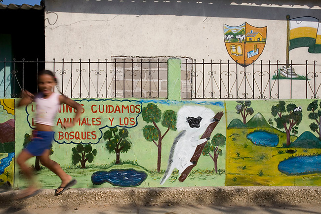 Young girl runs past mural in her small village of Los Limites, Colombia, which promotes protection of the Cotton-top tamarin.
