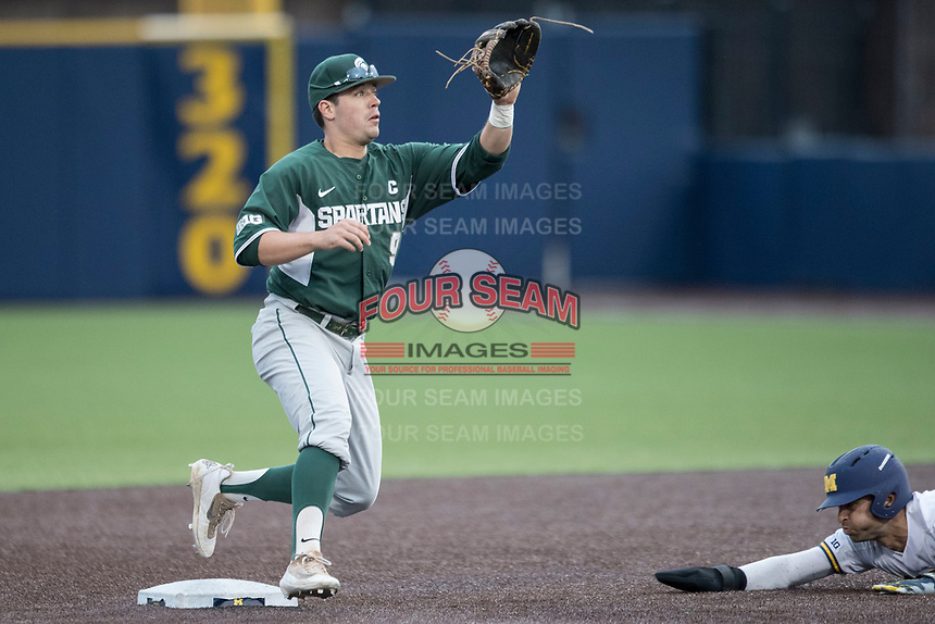 Michigan State Spartans second baseman Dan Durkin (9) waits for a throw as Michigan Wolverines baserunner Jonathan Engelmann (2) slides into the base on May 19, 2017 at Ray Fisher Stadium in Ann Arbor, Michigan. Michigan defeated Michigan State 11-6. (Andrew Woolley/Four Seam Images)