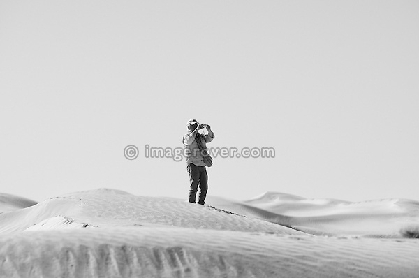 Africa, Tunisia, nr. Tembaine. Desert traveller Gernot photographing in the dunes close to Tembaine on the eastern edge of the Grand Erg Oriental. --- No releases available, but releases may not be needed for certain uses. Automotive trademarks are the property of the trademark holder, authorization may be needed for some uses.  --- Info: Image belongs to a series of photographs taken on a journey to southern Tunisia in North Africa in October 2010. The trip was undertaken by 10 people driving 5 historic Series Land Rover vehicles from the 1960's and 1970's. Most of the journey's time was spent in the Sahara desert, especially in the area around Douz, Tembaine, Ksar Ghilane on the eastern edge of the Grand Erg Oriental.