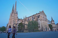 The Saint Andre Cathedral 11th 12th century with its majestic twin gothic towers in the evening at sunset on the place pey berland in Bordeaux, two young women walking on the square city Bordeaux Gironde Aquitaine France