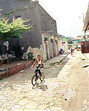 PANAMA, Portobello, a boy rides his bicycle on the street in Portobello