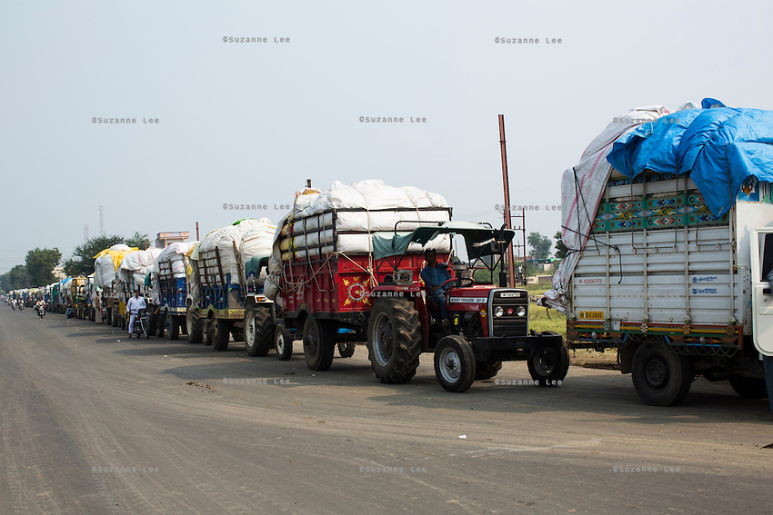 A long line of trucks and tractors wait in queue at a cotton ginning factory in Maheshwar, Khargone, Madhya Pradesh, India on 13 November 2014. Photo by Suzanne Lee for Fairtrade