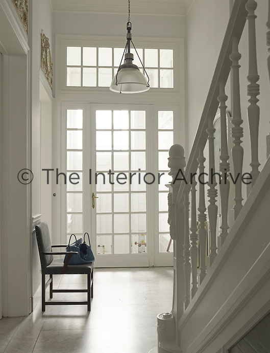 The generous double-height entrance hall has been painted white to enhance the sense of space